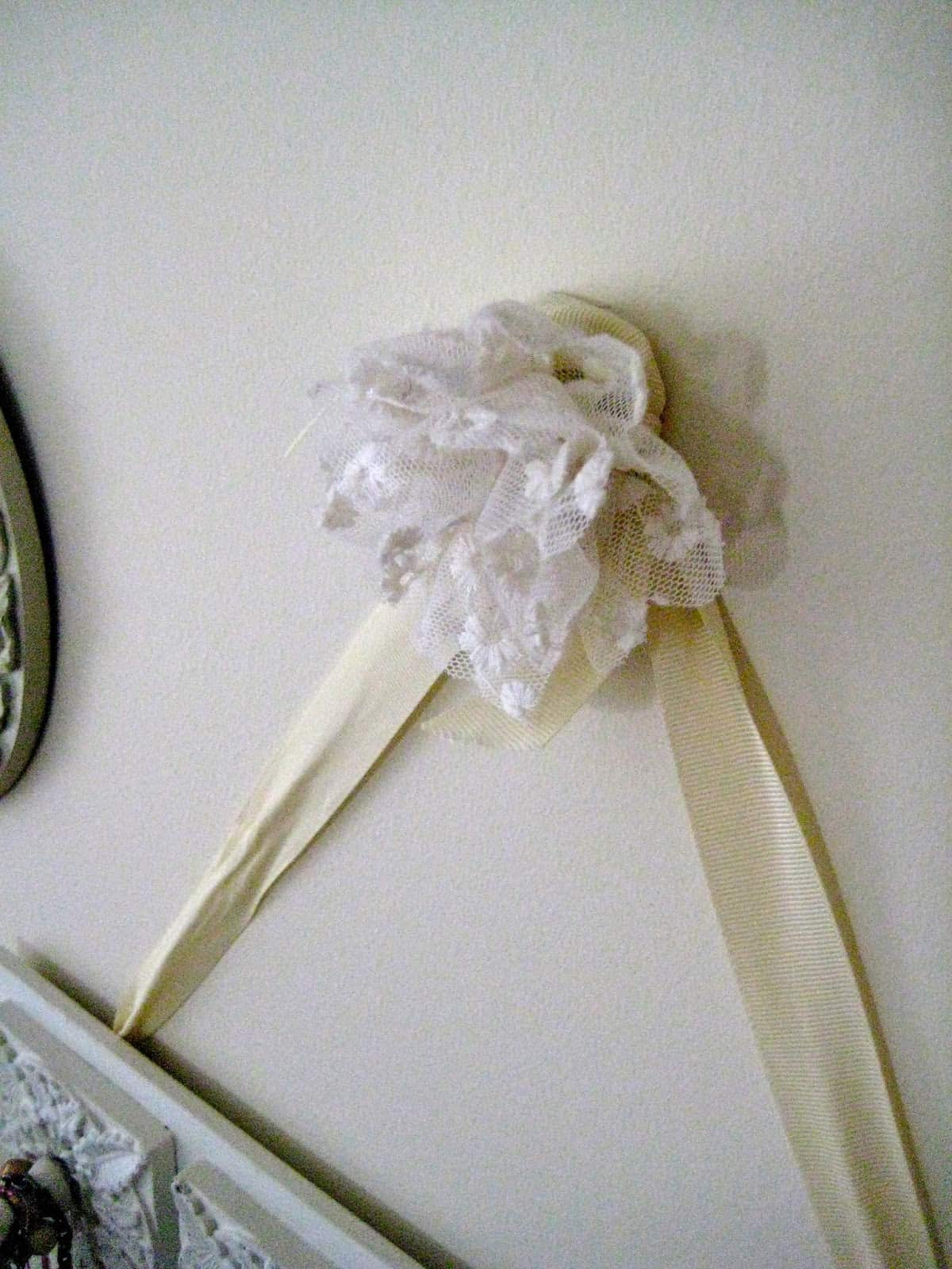 a lace flower hanging on a wall over a ribbon