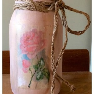 a mason jar painted pink with an image transferred onto it
