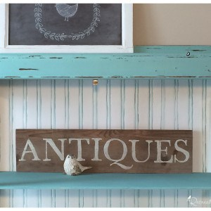 hand painted antiques sign inside of a recreated bookcase