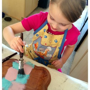 child painting a wooden bowl with pink and blue paint