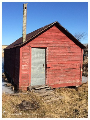 rustic metal door on a building with chippy red paint