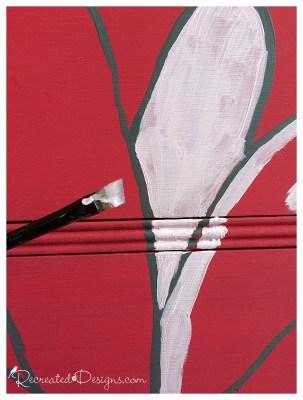 painting a large flower on a vintage dresser