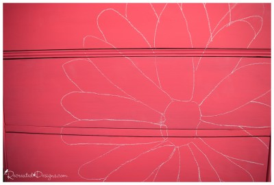 a chalk outline of a large flower on a painted dresser