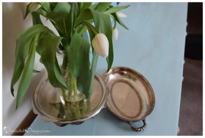 white tulips and silver trays on a blue painted dresser