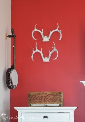 painted antlers on a red wall