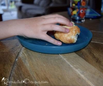 a little hand grabbing a piece of bread