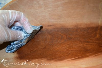 rubbing on General Finishes Gel Stain in Nutmeg onto a raw wood bread bowl