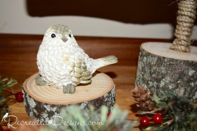 a little bird sitting on a wood slice surrounded by greens and berries
