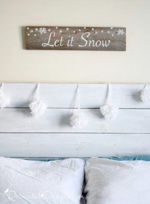 bedroom headboard dcorated with pom pom snowballs and a let it snow sign