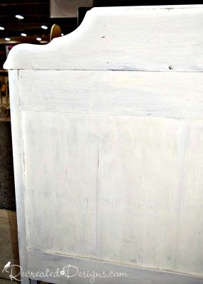 the painted back of a vintage wood dresser