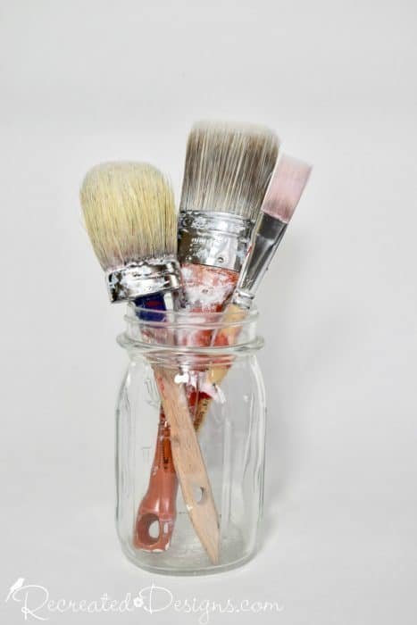 a jar with paint brushes