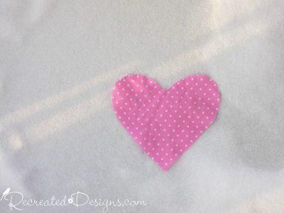 pink polka dot heart laying on snow