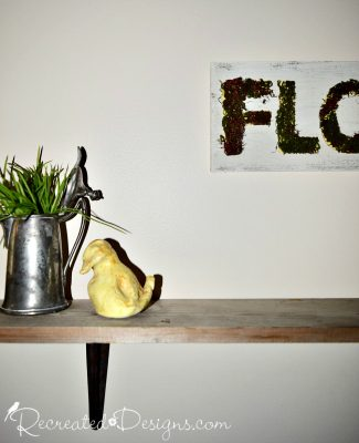 silver pitcher with grass and little yellow duck on a wood shelf