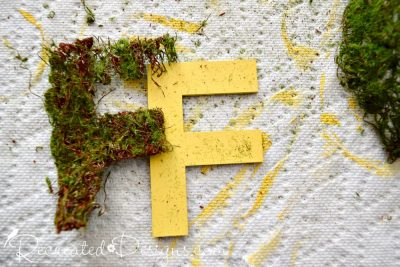cutting moss ribbon to cover yellow painted letters