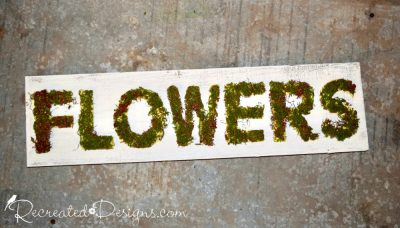 reclaimed wood sign with moss covered letters