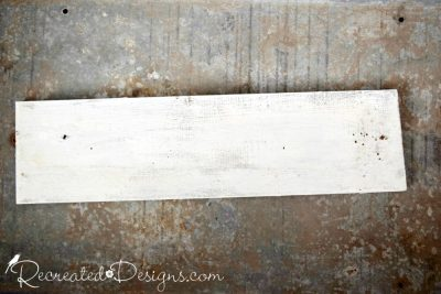 a piece of reclaimed wood painted white