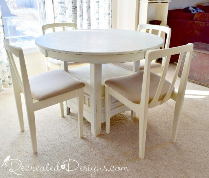 a dark coloured dining set painted with cream coloured paint