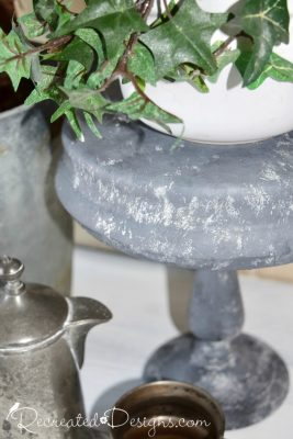 a thrift store bowl and candle holder painted to look like galvanized metal