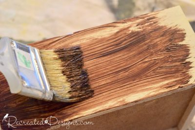 Applying General Finishes Gel Stain in Nutmeg with a chip brush to painted pine