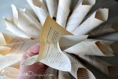 crinkling up an old book page cut into a square to make the centre of a paper flower