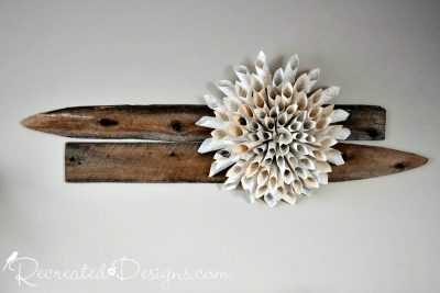 a paper Chrysanthemum make out of old book pages hanging on two pieces of reclaimed wood