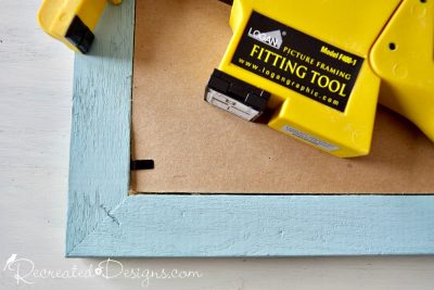 using a fitting tool to add clasps to the back of a frame to hold everything in place