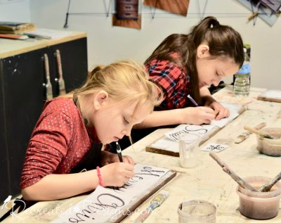 kids painting rustic signs using Miss Mustard Seed Milk Paint during a class in Ottawa, Ontario