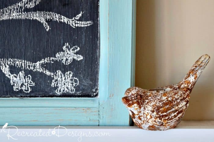 a little rusty bird sitting next to chalk blooms