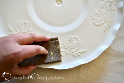 sanding the high points of a painted silver tray