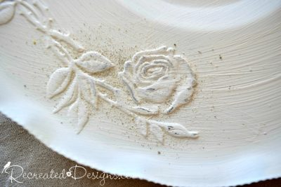 sanding off the high points of a rose pattern on a vintage tray that is painted