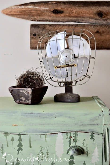 Vintage fan, bird's nest and antique berry box sitting on top of a Canada 150 themed dresser