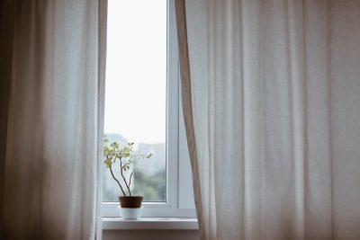 white curtains over a window with a plant on the ledge