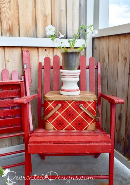 old red chair with a vintage picnic basket and a planter