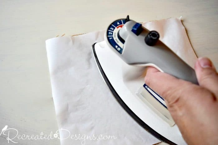 ironing on the freezer paper to the back of some burlap
