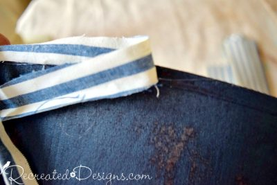 attaching a strip of new fabric with hot glue to cover up a old salvaged lamp shade