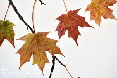 attaching leaves to canvas with adhesive glue