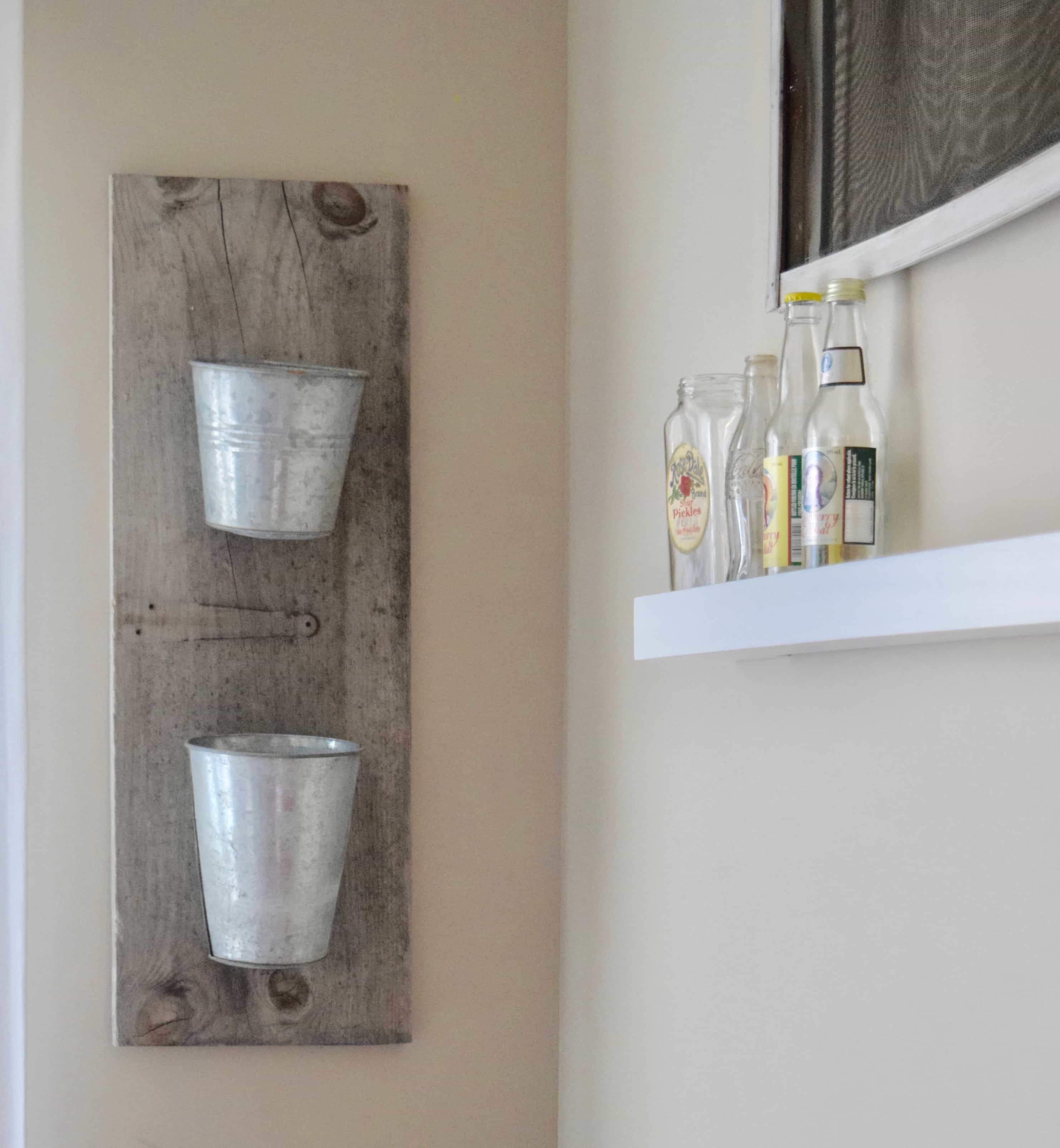 hanging salvaged buckets on reclaimed wood for plants