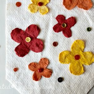 hot gluing on vintage buttons and paint dyed flowers