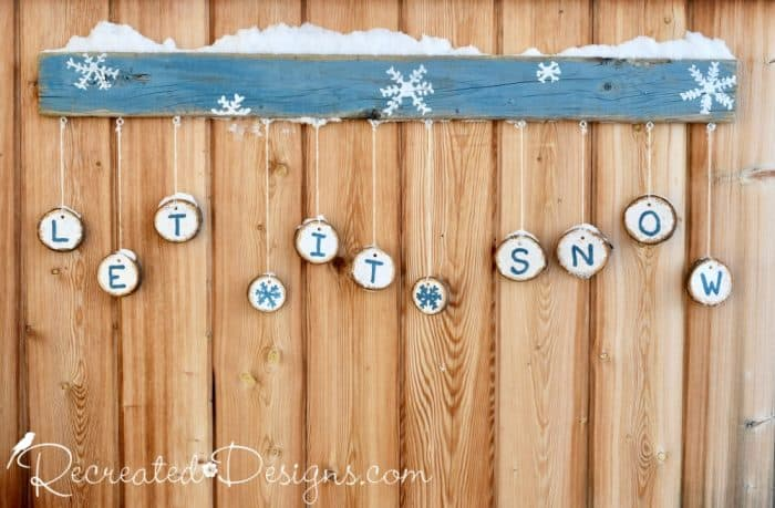Let it Snow sign hanging on a fence