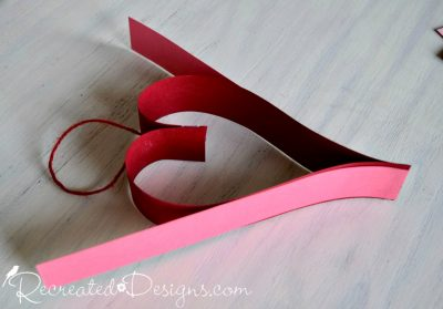 adding hearts to a paper Valentine garland by Recreated Designs