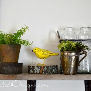little yellow wrought iron bird sitting on a wood shelf