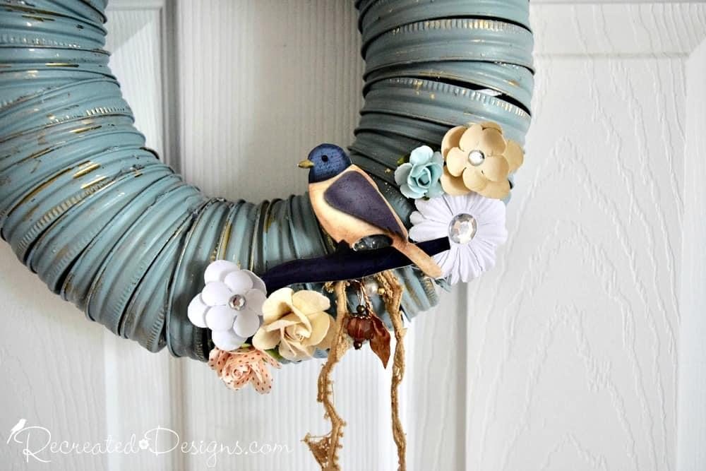little bird sitting amongst paper flowers on a diy wreath