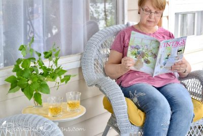 reading a magazine on a cottage porch in the summer