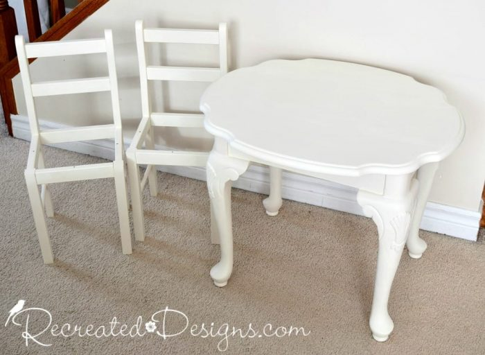 A mismatched side table and two small chairs painted with Country Chic Paint in Vanilla Frosting