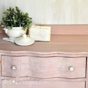 vintage Ironstone on top of a pink painted dresser