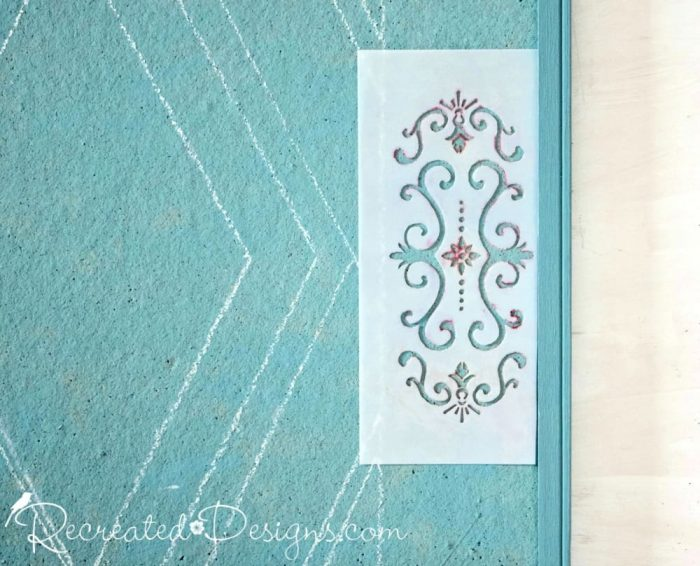 using a stencil to add a pattern to a painted cork board