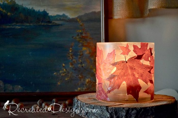 a beautiful glass candle holder covered with real Maple leaves