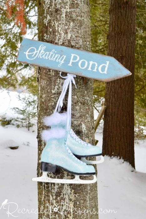 painted skates hanging with a Skating Pond sign