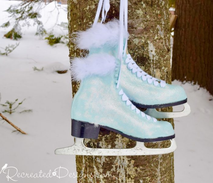 painted skates hanging on a tree in the snow