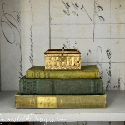 old books stacked in a painted bookshelf